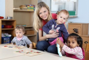 Erzieherin am Tisch mit Kinder beim Puzzeln